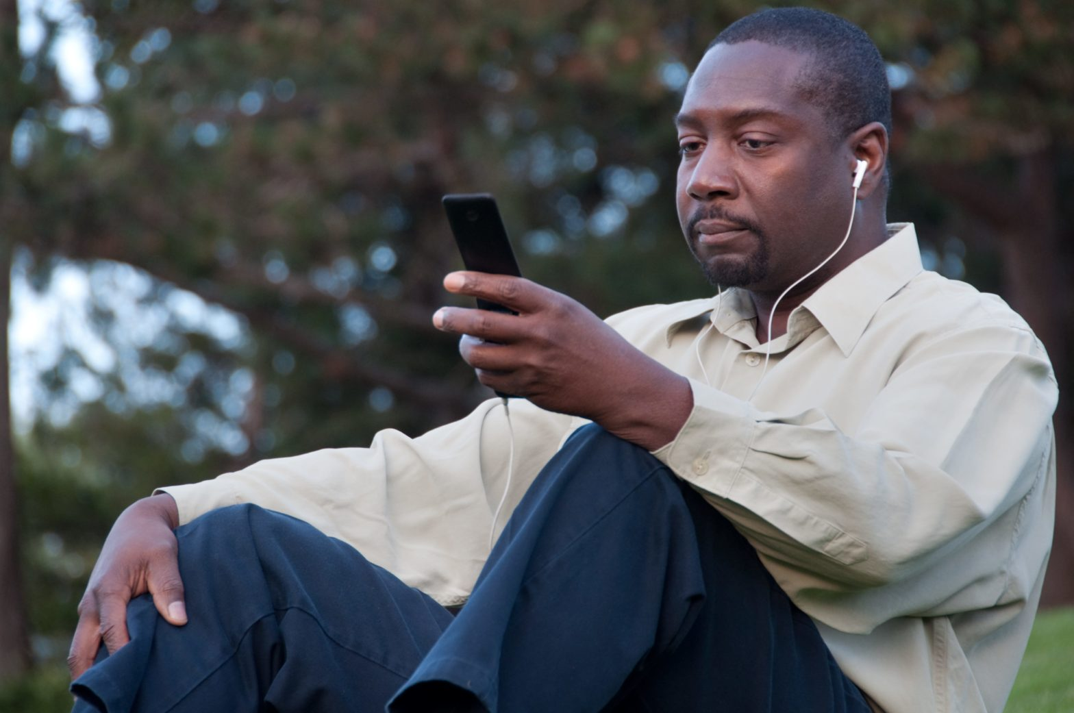 Man sitting and using his phone with earbuds