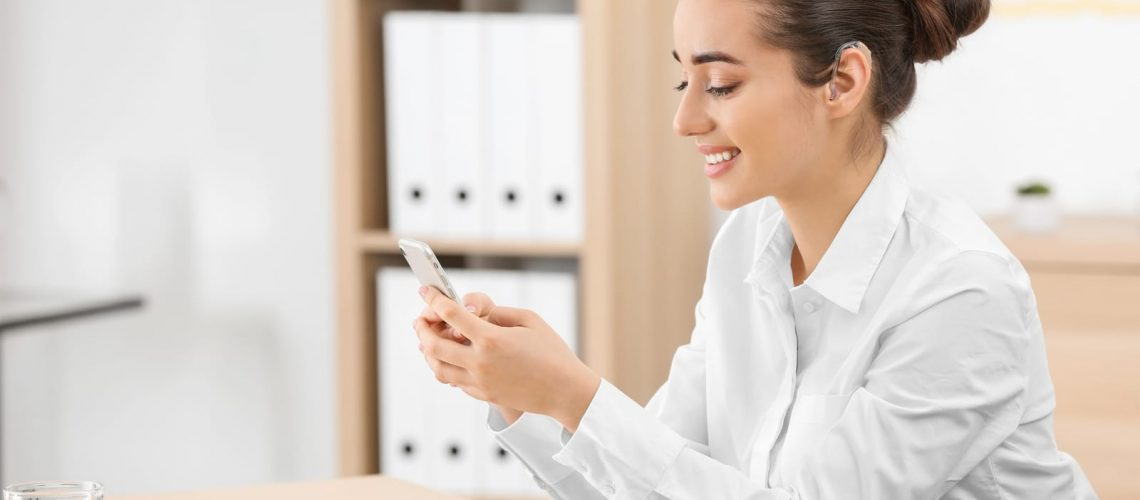 Young woman with hearing aid using smartphone indoors